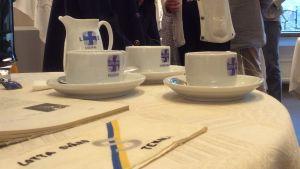 Kaffekoppar och en kaffekanna samt en servett med Lotta Svärd-emblem. Äldre kvinnor syns i bakgrunden.