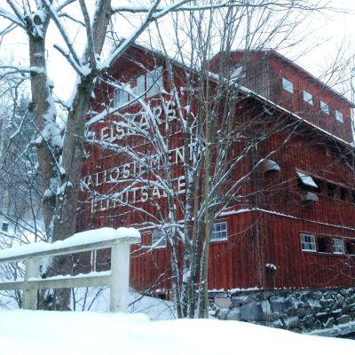 En stor röd gammal träbyggnad vid en liten å. I gaveln står det Fiskars Valiosiementä Elitutsäde. Vinter, snö på träden.
