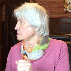 Puolilähikuva vanhasta naisesta, joka katsoo oikealle. Hänen päällään on vaaleanpunainen neule ja kaulassaan beigesävyinen silkkihuivi.