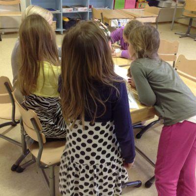 Barn bakifrån som står samlade bakom en pulpet.