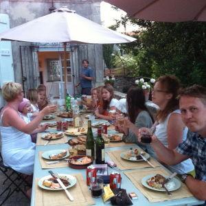 Kai Sadinmaan naapureita päivällisellä ranskalaisen talon pihalla.