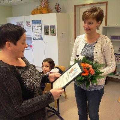 Nina Saarela belönar Sussi Backman med diplom.