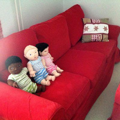röd soffa och tre dockor