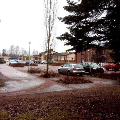 Bilar parkerade vid kommungården i Sjudenå. Affärer och andra hus syns också.