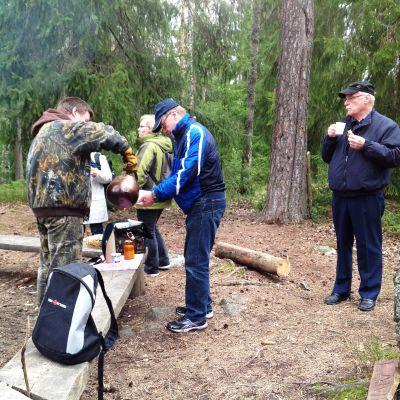 Män dricker kaffe i Sibbo storskog.