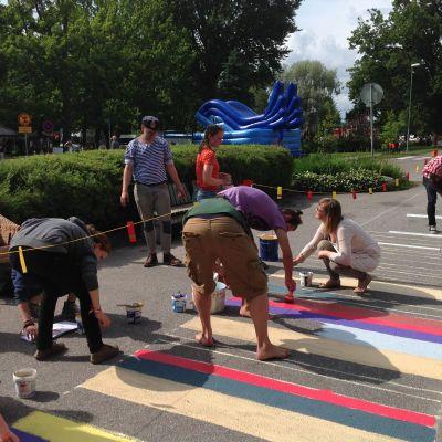 Människor målar en matta på asfalten.