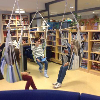 Kolme tyttöä riippukeinuissa oleskelutilassa, Hauhon yhtenäiskoulu