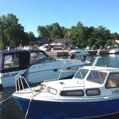 Båtar står förtöjda i en hamn.