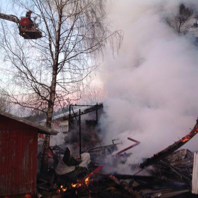 Maantasalle palanut varastorakennus, savuavat rauniot.
