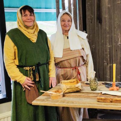 Två kvinnor i medeltida dräkter står bredvid ett stort träbord.