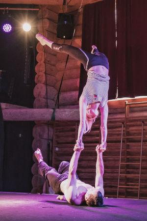Kaksi sirkustaiteilijaa tekemässä temppua, nainen seisoo käsillä selällään maassa makaavan miehen käsien varassa