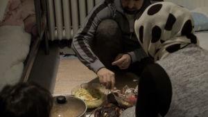 Familj äter middag på golvet i litet rum i nödinkvartering
