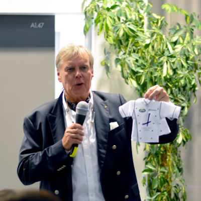 Nils-Gustav Höglund står med en mikrofon i ena handen och i den andra har han en liten miniatyrversion av en kocklandslagströja.