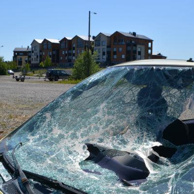 I Bakgrunden synns färggranna våningshus, i förgrunden en bil med trasig vindruta.