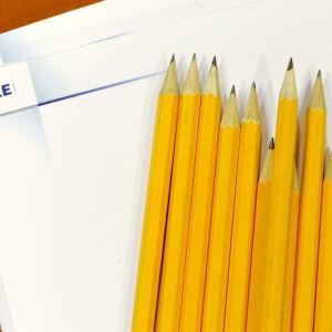 yle-logolla oleva paperilehtiö ja lyijykyniä v. 2008