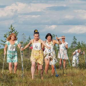 Fem personer klädda i blommiga sommarklänningar skidar över ett kärr. Två av personerna är programledarna Hannamari Hoikkala och Nicke Aldén.