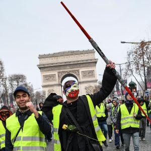Demonstranter i gula västar går längs framför triumbågen i Paris