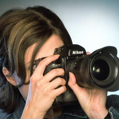Nainen tarkentaa kameraa.