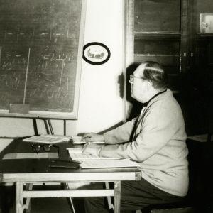 Gerald Moore istuu pöydän ääressä ja opettaa.