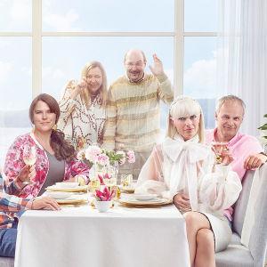 Alex, Anna, Mickan och Fredde sitter vid ett bord och ser rakt mot kameran. Bakom fönstret står Anette och Ove och vinkar.