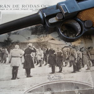 Valokuva joukko-osaston tarkastuksesta ja päällä Parabellum-pistooli.