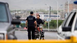 En polis stoppar en man av uiguriskt ursprung i Xinjiang.