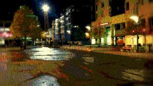 """Autiota Joensuun kaupungin keskustaa yöllä, sävypoistettu, """"taidekuvamainen"""" tunnelmakuva, ei väkeä, rakennuksia ja valoja vain"""