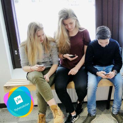Elever sitter på en skolbänk och surfar på sina telefoner.