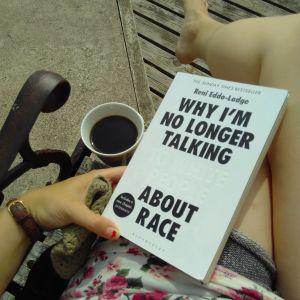 Barbent person läser bok med en kopp kaffe.