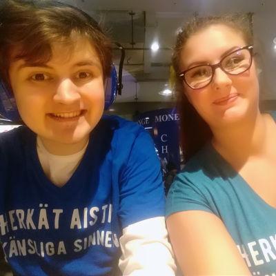 """En pojke med öronskydd och en kvinna med långt hår och glasögon. På deras tröjor står det """"Herkät aistit Känsliga sinnen""""."""