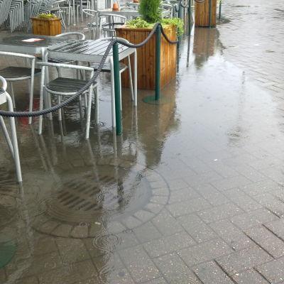 Översvämmad dagvattenbrunn vid café.