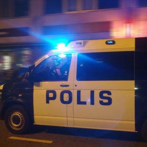 Polisbil på uppdrag på natten.