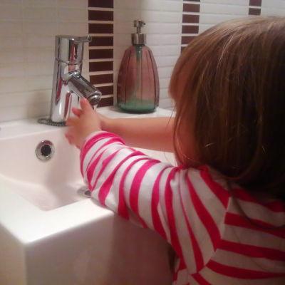 Flicka tvättar händerna.