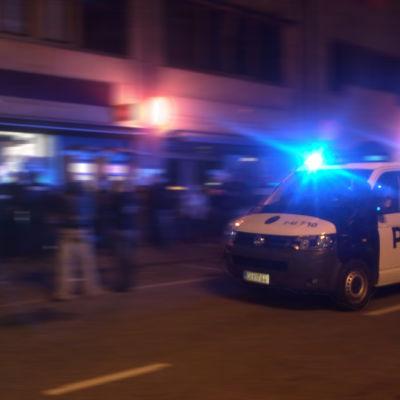 Polisbil på uppdrag på natten i Borgå. Nyfikna ungdormar på gatan.