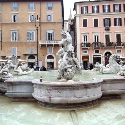 Monin veistoksin koristeltu suihkulähde Piazza Navonalla Roomassa, taustalla punertavia rakennuksia.