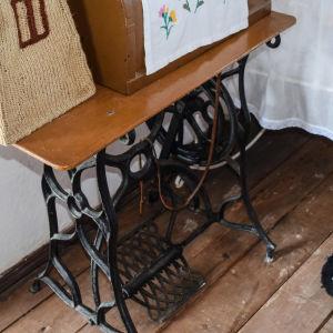 En gammal trampsymaskin med maskinen i en kupa på bordet.
