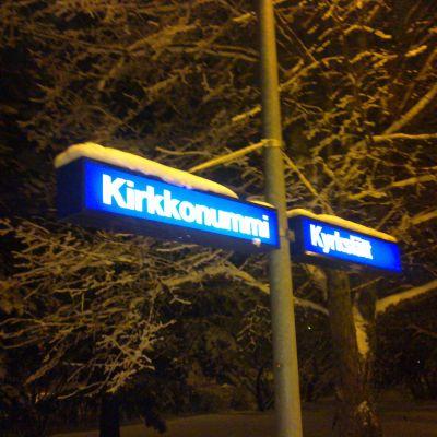 Ortnamnsskylt på Kyrkslätt station i vintertid.