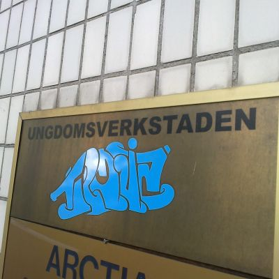 """Plakat på väggen. På plakatet står det """"Ungdomsverkstaden Troja"""""""