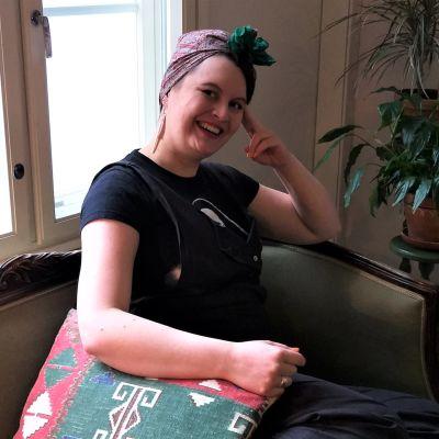 Hymyilevä Jonna Nummela istumassa sohvalla.