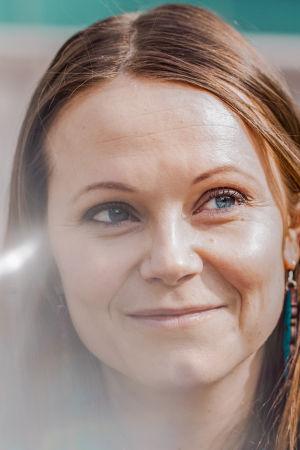 Punertavahiuksinen nainen katsoo hymyillen oikealle yläviistoon, lähikuva rajattu kaulasta alaspäin.