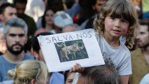 Ett barn som håller upp ett plakat med en jaguar på i en demonstration mot skövlingen av Amazonas regnskog.