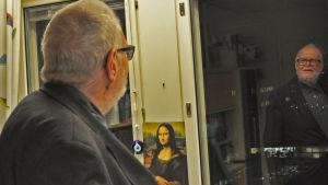 Atte Blom ser sin spegelbild i ett fönster