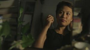 En kvinna står framför spegeln och gör sig i ordning för en kväll på stan.