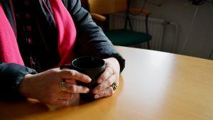 En kvinna sitter vid ett bord med en kaffekopp i händerna. Kvinnans ansikte syns inte på bilden.