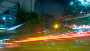 Liikennettä ja taloja, värikkäitä valojuovia kuvan päällä