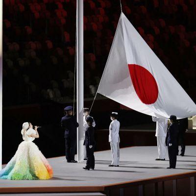 Den japanska nationalsången sjungs av en en kvinna i fluffig och färggrann klänning när den japanska flaggan hissas inne på olympiastadion i Tokyo.
