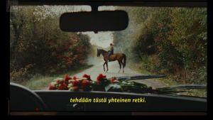 Nainen ratsailla metsätiellä, ruudussa teksti tehdään tästä yhteinen hetki.