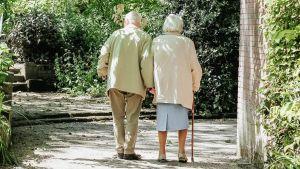 Ett äldre par som promenerar på en sandväg