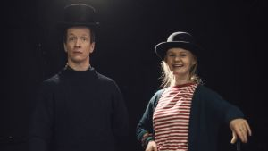 Markus Haakana och Emma Nordblad står på en mörk scen med höga svarta hattar på huvudet.