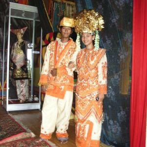 Förmögna minangkabauers bröllop är färgstarka. På bilden ett brudbar i orangea traditionella kläder och guldig huvudbonad.